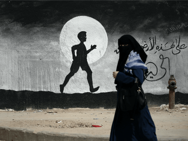 A Palestinian woman walks past a graffiti painted on a wall of the United Nations school of Beit Hanun, in the northern Gaza Strip, on May 9, 2016.