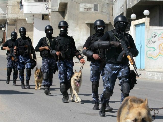 Palestinian Hamas policmen march with their police dogs along a street in Gaza City on April 24, 2013.