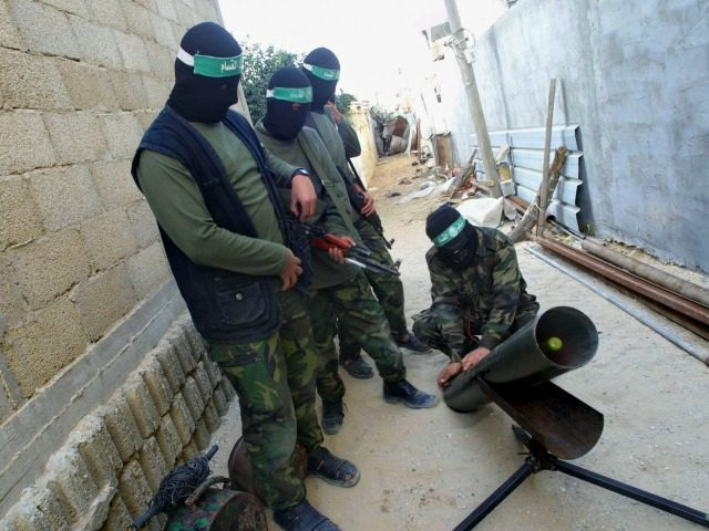 Masked Palestinian gunmen from the militant group Hamas prepare to fire a homemade rocket at Israeli forces in the area where an Israeli Army bulldozer demolished a structure near the border with Egypt, November 29, 2003 in the Rafah refugee camp, southern Gaza Strip.