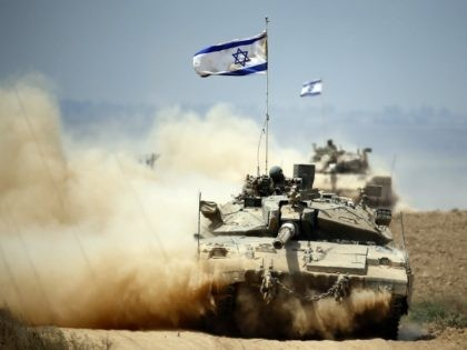 Israeli Merkava tanks roll near the border between Israel and the Gaza Strip as they return from the Hamas-controlled Palestinian coastal enclave on August 5, 2014, after Israel announced that all of its troops had withdrawn from Gaza.