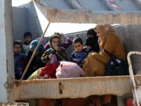 IRAQ, Karbala : Iraqi women and children, who fled Fallujah, sit in the back of a truck as they wait at an army checkpoint at Ayn al-Tamer crossing at the entrance to Karbala province on January 6, 2014. Buses and cars carrying families fleeing the fighting in Fallujah and Ramadi …