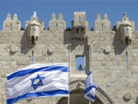 Israeli youths wave their national flag as they take part in the 'flag march' through Damascus Gate in Jerusalem's old city during celebrations for Jerusalem Day on May 17, 2015 which marks the anniversary of the 'reunification' of the holy city after Israel captured the Arab eastern sector from Jordan …