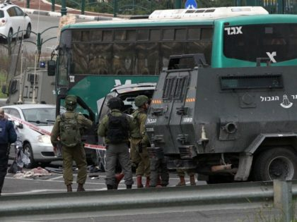 Israeli security forces stand guard at the scene where three Palestinians carried out two attacks -- a shooting and a car ramming -- on Israelis at a bus stop at the entrance of the Israeli settlement of Kiryat Arba in the southern occupied West Bank before they were shot dead …