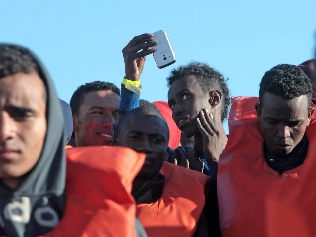 Migrants and refugees disembark from a Maltese coast guard patrol vessel after being rescued at sea, on April 15, 2016, at the Messina harbor in Sicily.
