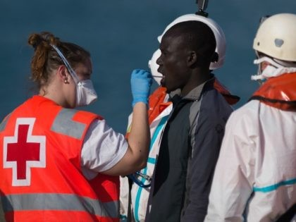 A man is attended by a Red Cross nurse on arrival into the southern Spanish port of Malaga on May 19, 2016 after an inflatable boat carrying 52 Africans, ten of them women, was rescued by the Spanish coast guard off the Spanish coast.