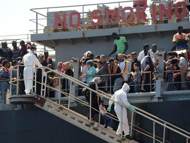 A picture taken at sea shows the transfer of immigrants from the tanker 'Torm Lotte' to tug boat 'Grifone' in the middle of Messina's marine channel following a rescue operation on July 20, 2014.