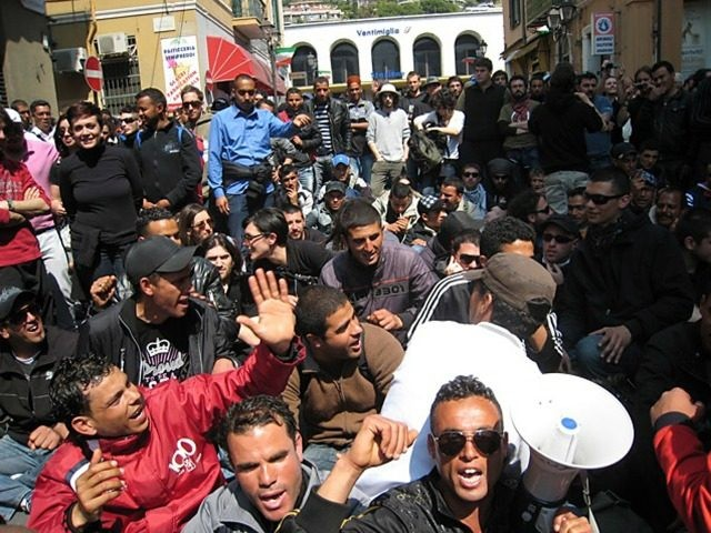 Around 60 mainly Tunisian migrants and a group of French and Italian activists demonstrate in front of the train station of the Italian border town of Ventimiglia after France cancelled trains due to cross the border to thwart migration demonstrations.