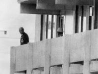 Picture taken on September 5, 1972 shows a Palestinian guerilla member (C) appearing on the balcony of the Israeli house watching an official (L) at the Munich Olympic village.