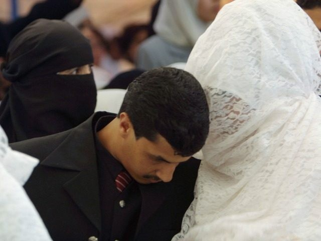 AMMAN, JORDAN - JULY 25: A Groom listens to his veiled bride in a mass wedding July 25, 2003 in Amman, Jordan. One hundred and four brides and grooms made the knot in a mass wedding organized by the Islamic society of (al-Afaf) for philanthropic wedding, celebrating with their families …
