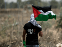 A Palestinian youth waves the national flag as Israeli military digs in search of smuggling tunnels at the border east of Gaza city on May 15, 2016, on the 68th anniversary of the 'Nakba'.