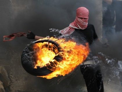 A Palestinian sets fire to a tyre during clashes between hundreds of Palestinians and Israeli soldiers outside the Ofer prison after a march marking the 65th Nakba day or 'Day of Catastrophe' on May 15, 2013 in Betunia near the West Bank city of Ramallah.