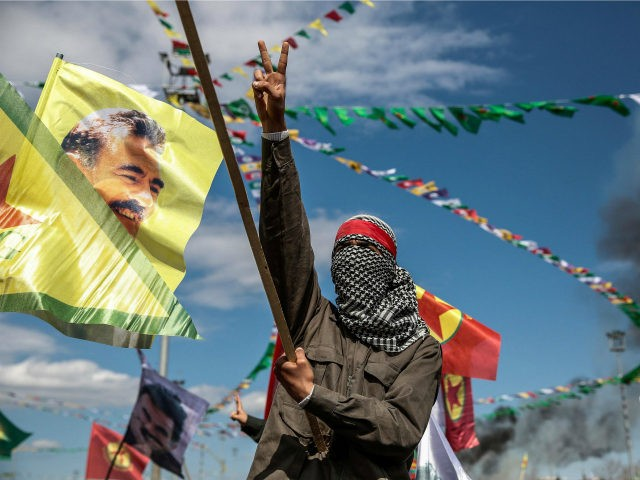TURKEY, Diyarbakir : DIYARBAKIR, TURKEY - MARCH 21: A Kurdish man wearing a mask flashes the v-sign as he holds up a flag with a picture of the jailed PKK leader Abdullah Ocalan during Newroz celebrations, on March 21, 2015 in Diyarbakir, Turkey. Thousands of Kurds gather for the Newroz spring festival in Diyarbakir in southeast Turkey under tight security after months of fighting between security forces and Kurdish separatists, and a series of bombings in Istanbul and Ankara. (Photo by Ulas Tosun/Getty Images)