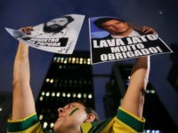 A demonstrator holds banners as she takes part in a protest against Brazil's President Dilma Rousseff's appointment of Brazil's former President Luiz Inacio Lula da Silva as her chief of staff, at Paulista avenue in Sao Paulo, Brazil, in this file photo dated March 17, 2016.... REUTERS/NACHO DOCE