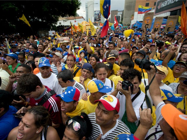 People chant against the government of President Nicolas Maduro during a march in Caracas, Venezuela, Saturday, May 14, 2016. The protesters are demanding that electoral officials accelerate the certification of the petition signatures that would kick off a recall of Maduro. (AP Photo/Ariana Cubillos)