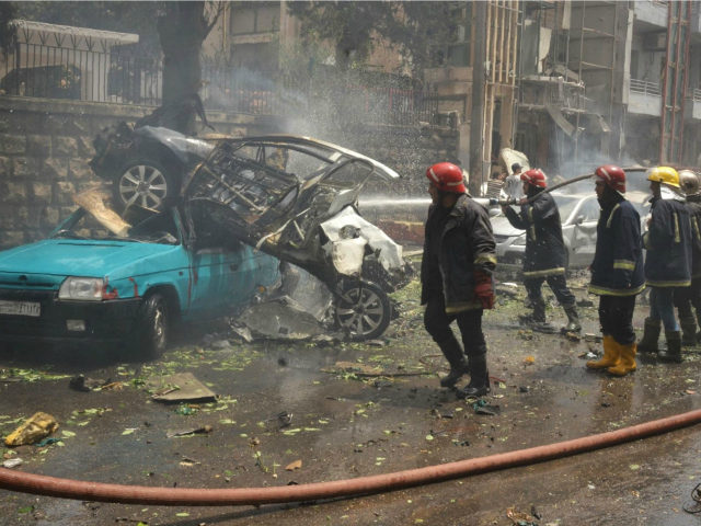 SYRIA, ALEPPO : Syrian emergency personnel secure a street after rockets reportedly fired by rebels hit Al-Dabbeet hospital in the government-controlled neighbourhood of Muhafaza in the northern city of Aleppo on May 3, 2016. The rebel fire on the hospital killed at least three women and wounded another 17 people, state news agency SANA said. / AFP PHOTO / GEORGE OURFALIAN