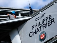 People work on the scoreboard above Court Philippe Chatrier after a piece of metal was blown off in high winds during the men's singles quarterfinal match between Kei Nishikori of Japan and Jo-Wilfried Tsonga of France on day of the 2015 French Open at Roland Garros on June 2, 2015 …