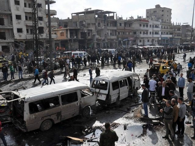 Syrians gather at the site of a double car bomb attack in the Al-Zahraa neighbourhood of the central Syrian city of Homs on February 21, 2016.