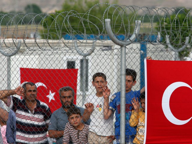 Migrants stand behind a fence at the Nizip refugee camp in Gaziantep province, southeastern Turkey, Saturday, April 23, 2016. German Chancellor Angela Merkel and top European Union officials, under pressure to reassess a migrant deportation deal with Turkey, are traveling close to Turkey's border with Syria on Saturday in a …