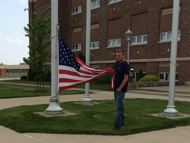 Photo of Ohio Teen Holding a Fallen American Flag Goes Viral Online
