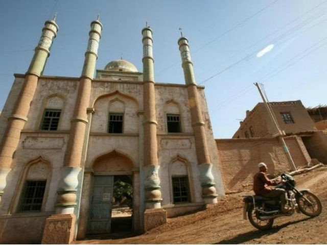 A man rides his motorcycle in front of a mosque at a village near the city of Turpan in China's remote far western region of Xinjiang, May 20, 2006.