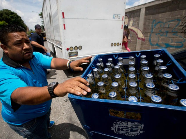 In this Friday, July 31, 2015, a Polar beer vendor makes his last weekend delivery to a liquor store in Caracas, Venezuela. Starting Monday, at least two of Polar's six beer plants is closing temporarily for lack of ingredients, affecting 25% of beer production in a country with one of the highest beer consumption rates in the world. Venezuela's President Nicolas Maduro blames food and goods shortages on an economic war waged by opposition aligned companies, while economists point to the country's price controls since 2003. (AP Photo/Fernando Llano)