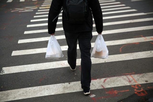 A man walks out of a store with plastic bags on May 5, 2016 in New York