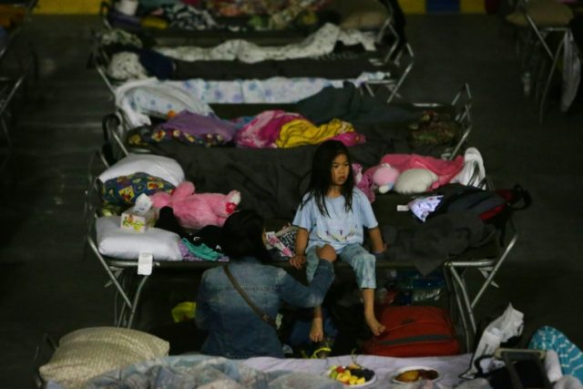 A young girl sits on a cot at a makeshift evacuee center in Lac la Biche, Alberta after fleeing forest fires north of Fort McMurray
