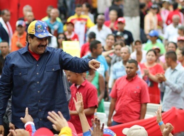 Venezuelan President Nicolas Maduro(L) greets supporters during a rally at the Miraflores presidential palace in Caracas