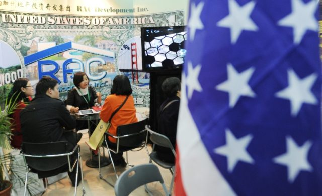 Potential Chinese real estate investors look at a display of United States property for sale at a property expo in Beijing
