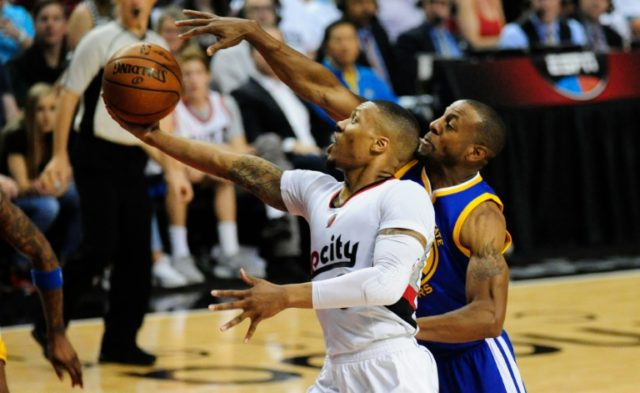 Damian Lillard of the Portland Trail Blazers drives to the basket on Andre Iguodala of the Golden State Warriors during Game Three of the Western Conference semifinals