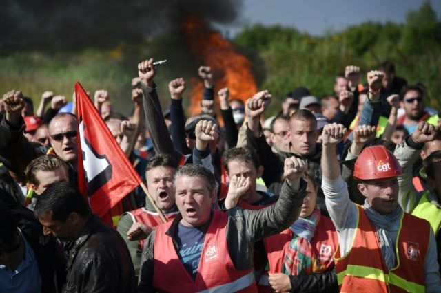 Striking workers are evacuated by French riot police as they block the access to an oil depot near the Total refinery of Donges, western France, to protest against the government's planned labour law reforms, on May 27, 2016