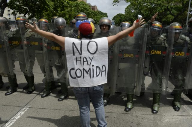 """A woman with a sign reading """"There is no food"""" protests against new emergency powers decreed by President Nicolas Maduro in front of police in Caracas"""