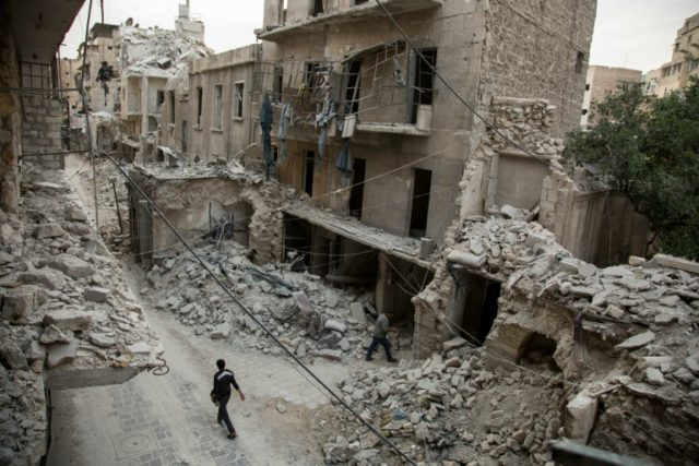 A Syrian man walks past destroyed buildings on May 2, 2016, in Aleppo's Bab al-Hadid neighbourhood which was targeted recently by regime air strikes