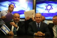 Israeli Prime Minister Benjamin Netanyahu (R) and Avigdor Lieberman (L), the head of hardline nationalist party Yisrael Beitenu, sign a coalition agreement on May 25, 2016 at the Knesset