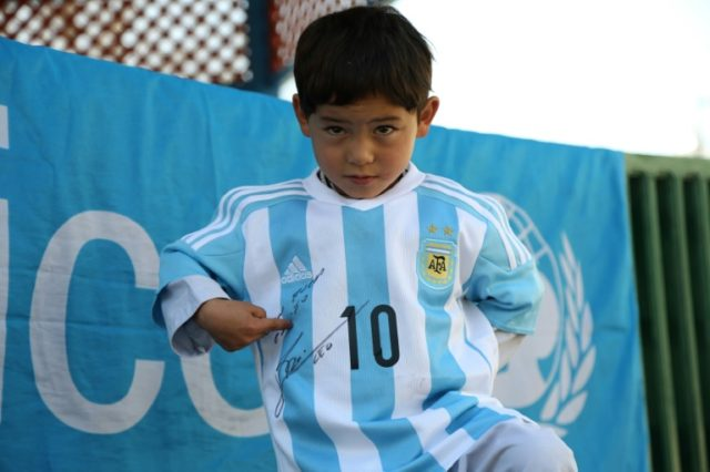 Afghan boy Murtaza Ahmadi proudly wears one of the jerseys sent by his idol Lionel Messi