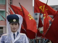 A North Korean traffic police woman directs vehicles at a street junction while behind her the sidewalk is decorated with flags of the ruling party, the Workers' Party on Thursday, May 5, 2016, in Pyongyang, North Korea. Members of North Korea's ruling party have gathered in Pyongyang ahead of their …