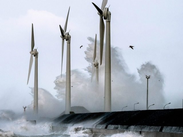 Waves break against the Boulogne-sur-mer harbour pier where wind turbines stand on February 8, 2016.