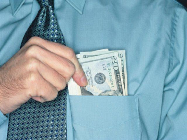 Businessman holding twenty dollar notes in shirt pocket, close-up