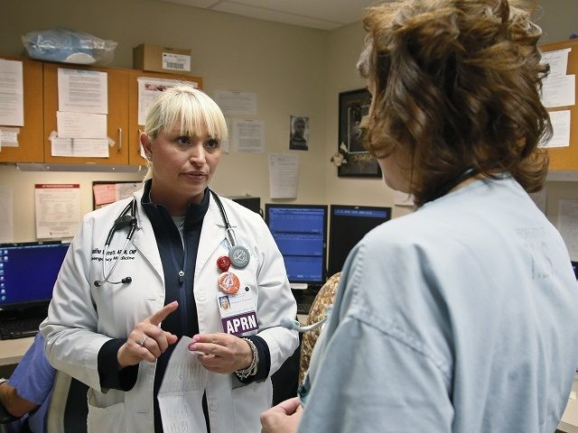 Jennifer Parrott, a certified nurse practitioner, left, talks with a doctor about a patient at the Oklahoma Health Sciences Emergency Department, in Oklahoma City, in Oklahoma City, Friday, May 13, 2016. Republican leaders in Oklahoma are moving toward a plan to expand its Medicaid program to bring in billions of …