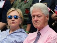 Democratic presidential candidate Hillary Clinton sits with her husband former President Bill Clinton as they attend a ceremony after walking in a Memorial Day parade Monday, May 30, 2016, in Chappaqua, N.Y. (AP Photo/Mel Evans)