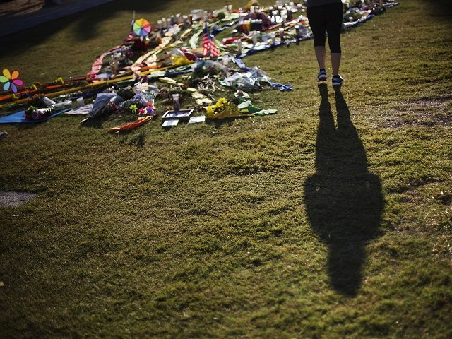 A woman casts a shadow while visiting a makeshift memorial downtown to the victims of the Pulse nightclub mass shooting Thursday, June 16, 2016, in Orlando, Fla. (AP Photo/David Goldman)