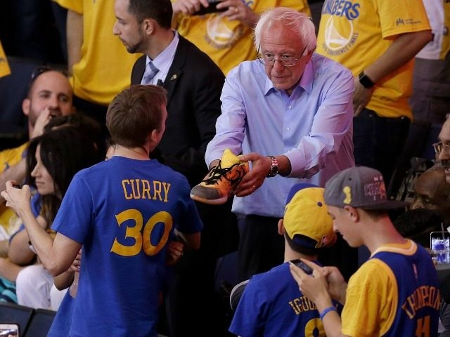 Democratic presidential candidate Sen. Bernie Sanders, I-Vt., hands a shoe to a fan during Game 7 of the NBA basketball Western Conference finals between the Golden State Warriors and the Oklahoma City Thunder in Oakland, Calif., Monday, May 30, 2016.