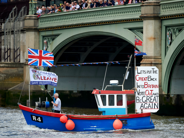 A boat decorated with flags and banners from the 'Fishing for Leave' group campaigning for a 'leave' vote in the EU referendum sail under Westminster Bridge toward the British Houses of Parliament as part of a 'Brexit flotilla' on the river Thames in London on June 15, 2016.
