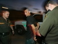 NOGALES, AZ - AUGUST 30: U.S. Border Patrol agents apprehend an illegal alien caught crossing the border August 30, 2005 in Nogales, Arizona. The governors of New Mexico and Arizona have declared a state of emergency along the border due to drug trafficking, illegal immigration and terrorism. (Photo by Sandy …