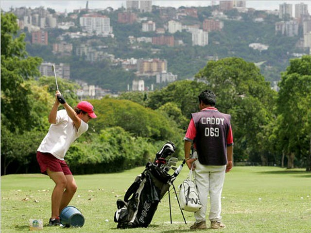 A member of the Country Club plays golf as his caddy stands by in Caracas, Venezuela, Tuesday, Aug. 29, 2006. The city mayor's office has decreed the expropriation of all three major golf courses in Caracas under eminent domain. (AP Photo/Leslie Mazoch)