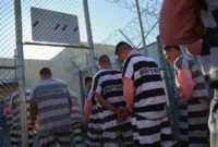 PHOENIX, AZ - MARCH 11: Immigrant inmates line up for breakfast at the Maricopa County Tent City jail on March 11, 2013 in Phoenix, Arizona. The striped uniforms and pink undergarments are standard issue at the facility. The tent jail, run by Maricopa County Sheriff Joe Arpaio, houses undocumented immigrants …