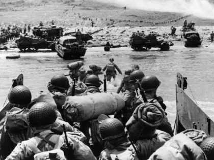 7th June 1944: American assault troops and equipment landing on Omaha beach on the Northern coast of France, the smoke in the background is from naval gunfire supporting the attack. (Photo by Fox Photos/Getty Images)
