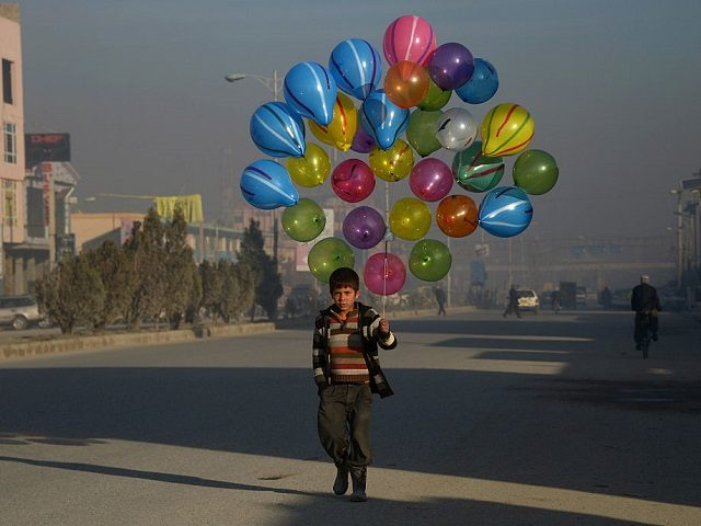TOPSHOT - Afghan boy Hizbullah, 10, walks as he looks for customers to buy his balloons on the streets of Mazar-i-Sharif on February 3, 2016. AFP PHOTO / Farshad Usyan / AFP / FARSHAD USYAN (Photo credit should read FARSHAD USYAN/AFP/Getty Images)