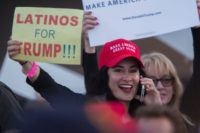 A woman hoods a sign expressing Latino support for Republican presidential candidate Donald Trump at his campaign rally at the Orange County Fair and Event Center, April 28, 2016, in Costa Mesa, California. Trump is vying for votes in the June 7 California primary election in hope of narrowing the …