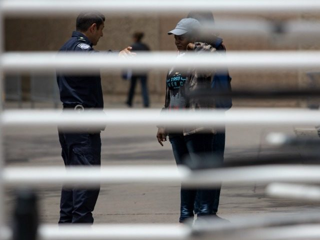 Migrants seeking for asylum in the United States, are seen talking to a Customs and Border Protection agent at the San Isidro Port of Entry, on May 26, 2016, in Tijuana, northwestern Mexico. On the past couple of weeks some 600 hundred migrants, mainly from Haiti and some African countries, …